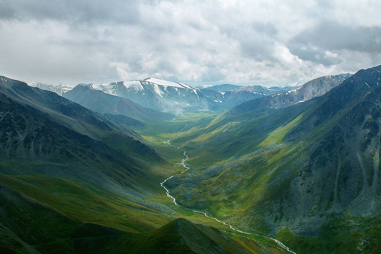 Green mountain gorge in summer with river, snow-capped peaks in the distance, sky with clouds