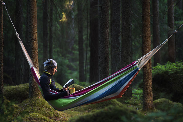 A man sitting in a hammock in a pine forest and reading a book Library Reading Relaxing Adventure Atmospheric Mood Book Forest Hammock Introvert Leisure Activity Lifestyles Men Moss Nature One Person Outdoors Pine Tree Plant Real People Sitting Taiga Tree Tree Trunk Trunk WoodLand Capture Tomorrow My Best Photo