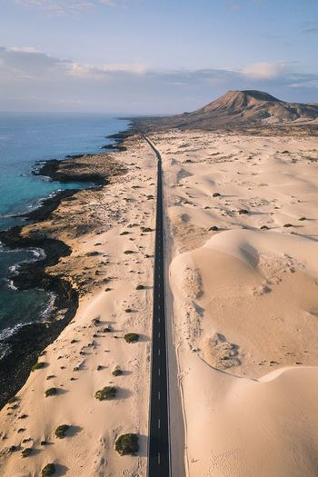 Road amidst sand by sea