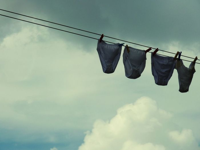 Low Angle View Of Panties Drying On Clothesline Against Cloudy Sky