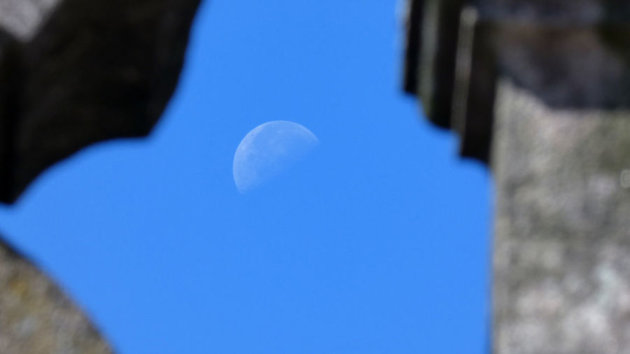 Low angle view of moon in blue sky