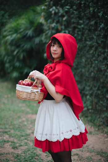 Woman in little red riding hood costume holding basket while standing against building