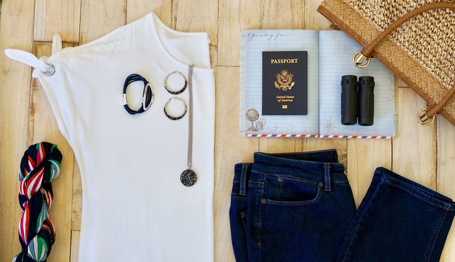 Flat lay image of clothes with traveling equipment on wooden table