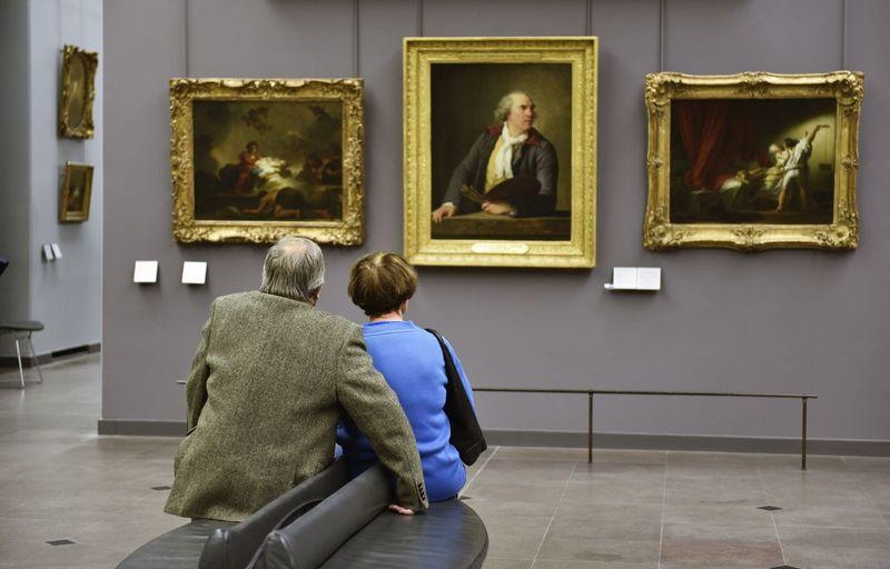 Rear view of man photographing woman in museum