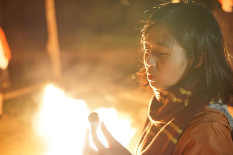 Close-up of woman holding marshmallow against campfire at night