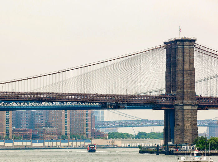 Low angle view of brooklyn bridge over river in city against clear sky