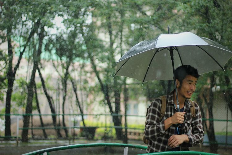 Umbrella Rain Wet People Front View Holding City Lifestyles Outdoors Smiling Nature Day One Man Only One Person Adult RainyDays Assignments Life Justexperiments