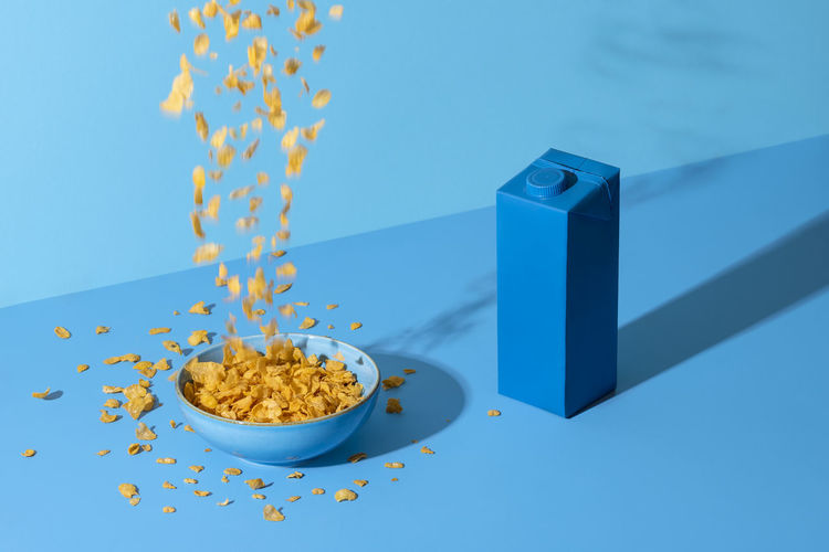 Pouring cereals in a bowl on blue table. breakfast table, cornflakes cereals in bowl and a milk box
