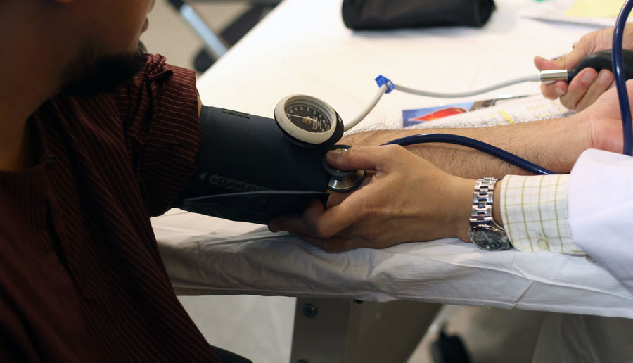 Cropped image of doctor examining patient arm with blood pressure gauge and stethoscope in medical clinic