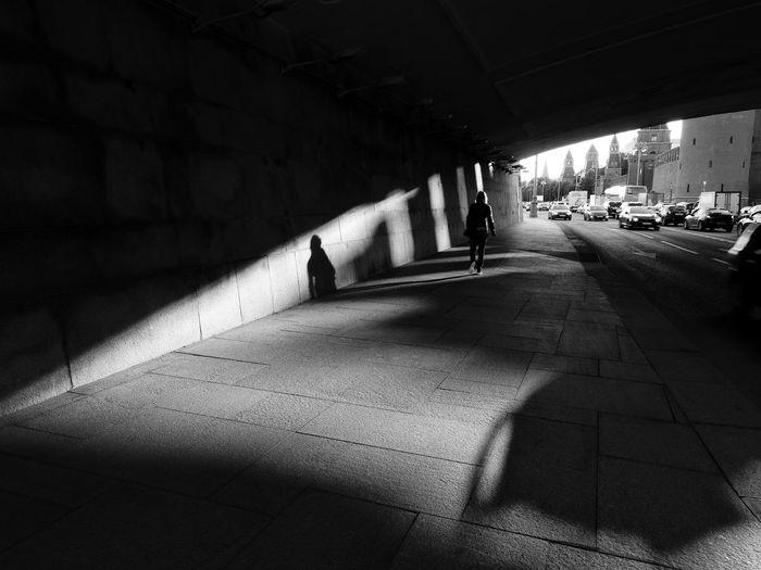 Silhouette woman walking on street in city