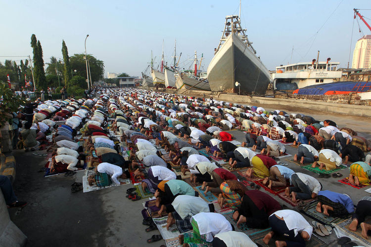 Crowd Praying At Commercial Dock Against Sky
