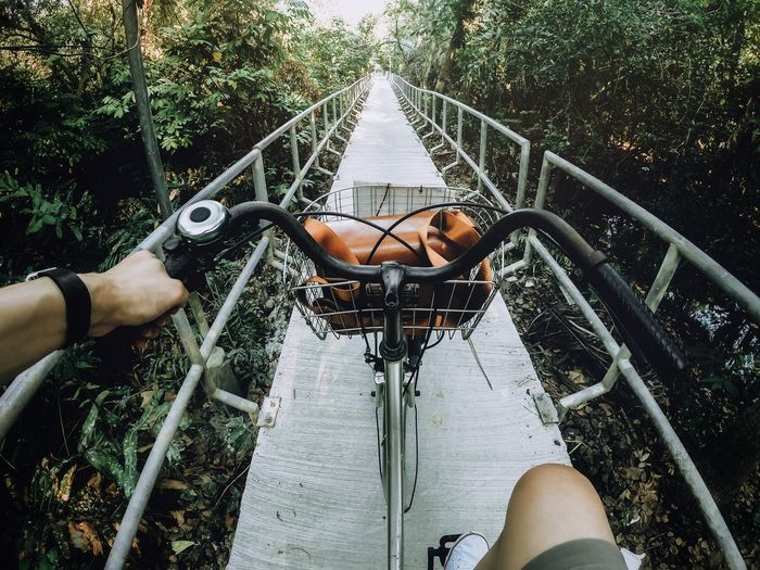 Low section of man riding bicycle on footbridge