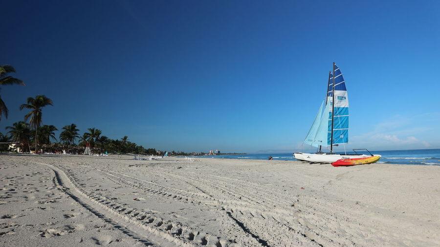 Sailboat on beach against clear blue sky