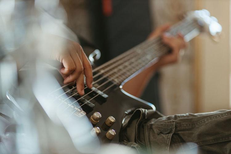 Close up musician playing bass guitar