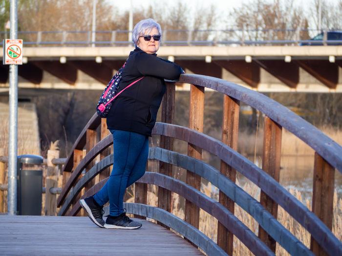 Portrait of woman standing on footbridge