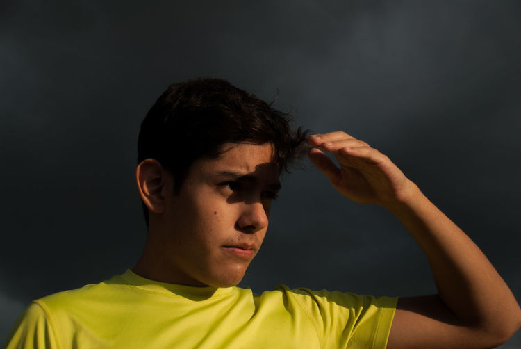 Thoughtful teenage boy shielding eyes against storm clouds