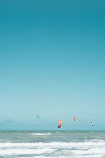 Scenic view of sea against clear blue sky and kite surf