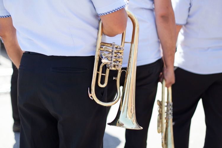 Midsection of men with trumpets