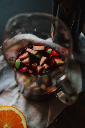 Close-up of chopped fruits in wine on glass jar at table