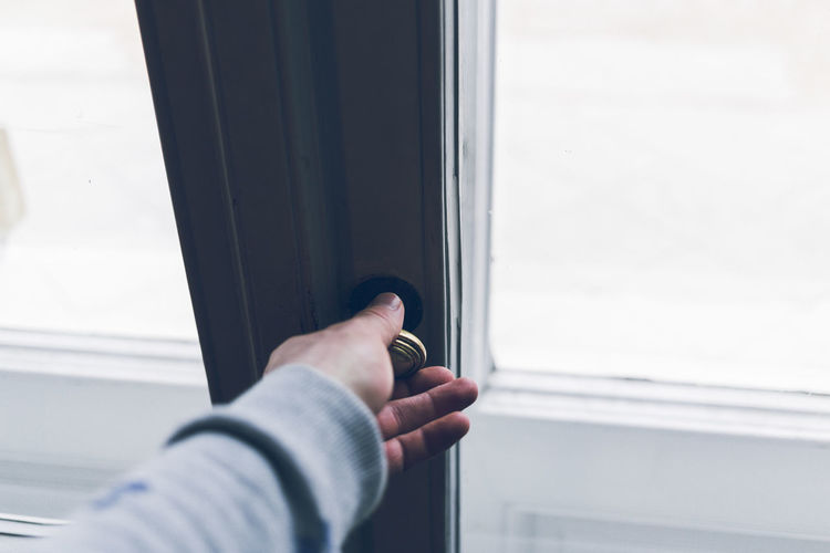 Cropped hand of person holding window knob