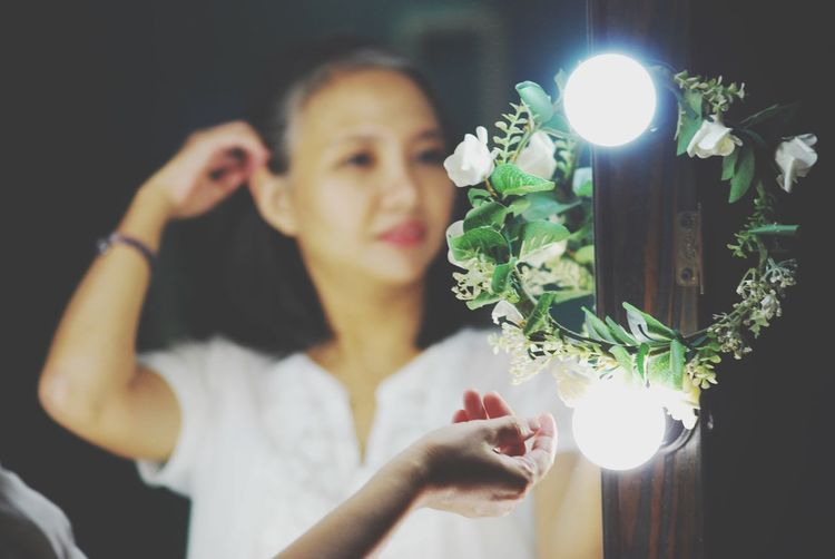 Woman touching illuminated decoration while reflecting on mirror