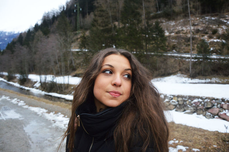 Young Woman Looking Away While Standing On Road During Winter