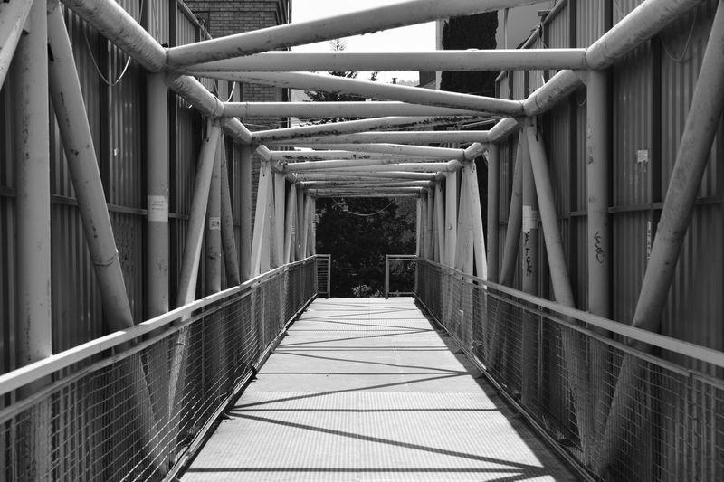 Narrow footbridge along railings