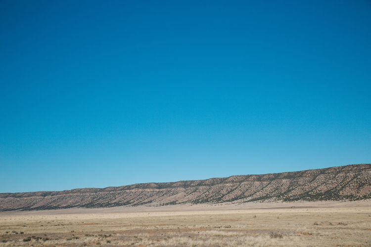Scenic View Of Arid Landscape Against Clear Blue Sky During Sunny Day