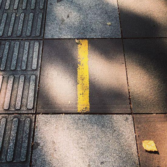 High angle view of arrow sign on sidewalk
