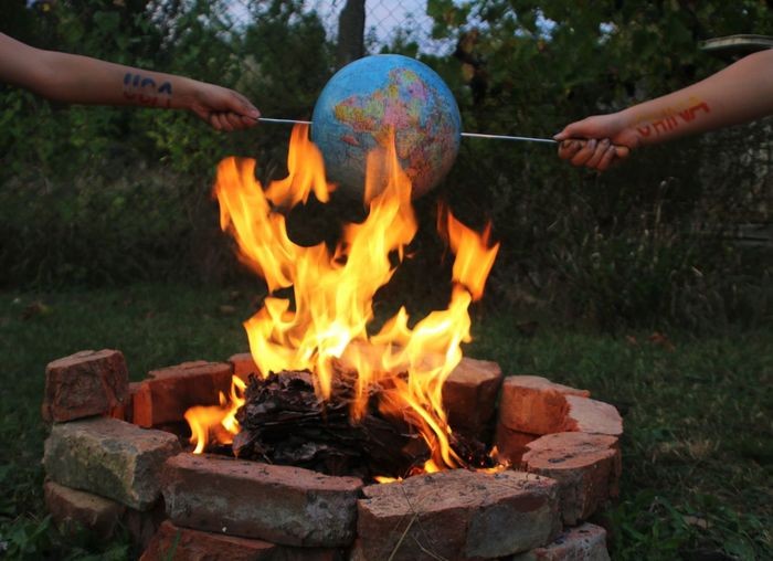 Cropped hands burning globe at fire pit in backyard
