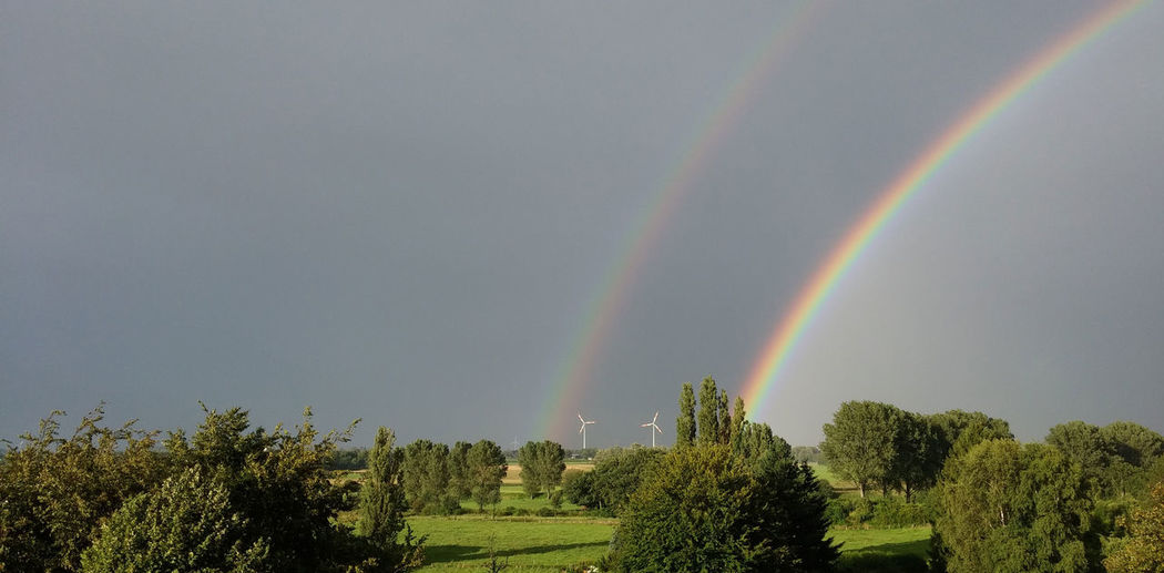 Scenic view of double rainbow over landscape against sky