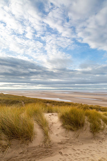 Looking out over marram grass covered sand dunes towards the sea, at formby in merseyside