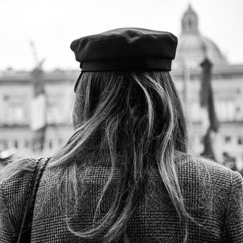 Rear view of woman wearing hat standing in city