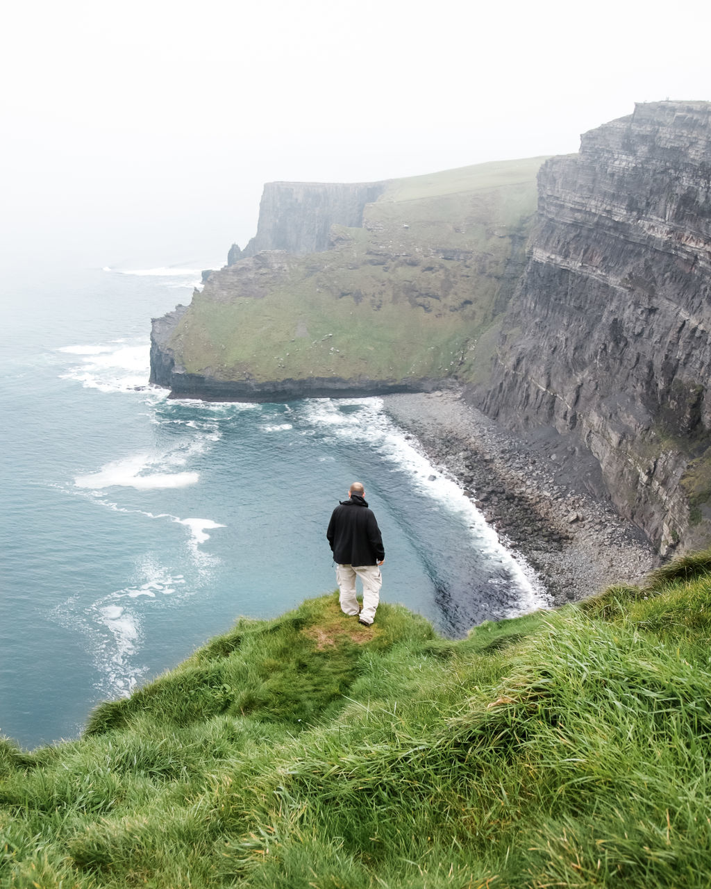 sea, nature, water, beauty in nature, real people, scenics, rear view, clear sky, rock - object, leisure activity, one person, outdoors, horizon over water, day, full length, motion, lifestyles, sky, wave, cliff, standing, beach, women, vacations, grass, young adult, people