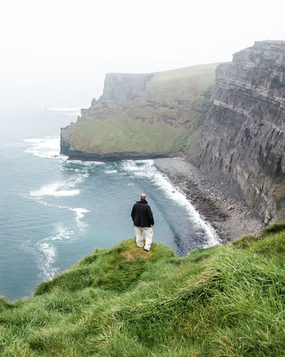 Adventure Ambition Beauty In Nature Cliff Cliffs Of Moher  Contemplation EyeEmNewHere Fog Foggy Landscape Full Length Grass Green Ireland Landscape_photography Lonely Meditation Misty Moody One Person Outdoors Rear View Standing The Great Outdoors - 2017 EyeEm Awards Tranquil Scene Wanderer