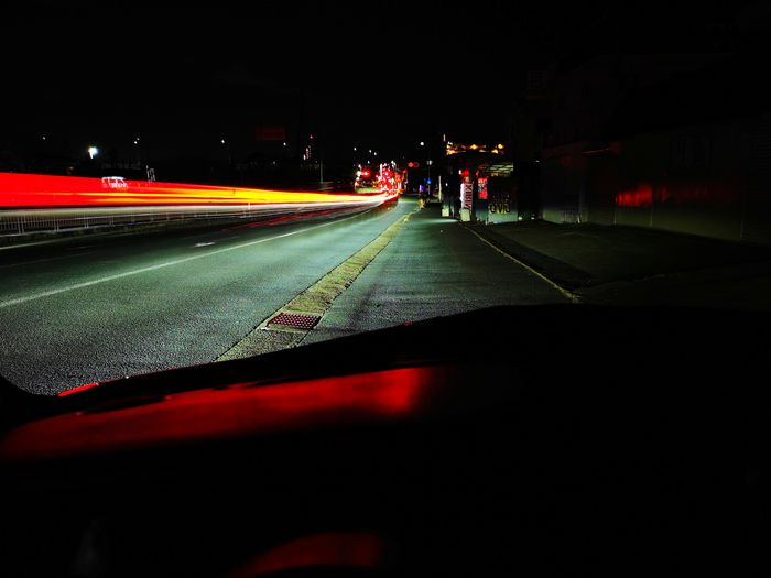 Light trails on road seen through car windshield at night