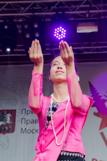 Indonesian dancer Adult Arms Raised Beautiful Woman Beauty Front View Hairstyle Human Arm Indoors  Jewelry Leisure Activity Lifestyles Looking Necklace One Person Pink Color Real People Standing Women Young Adult Young Women