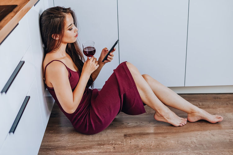 Young woman using phone while sitting on wooden floor