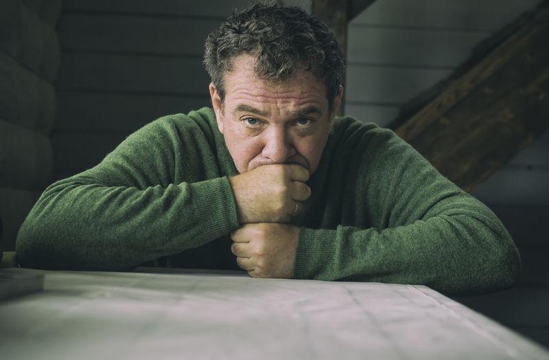 Portrait Of A Sad Man Sitting At Home