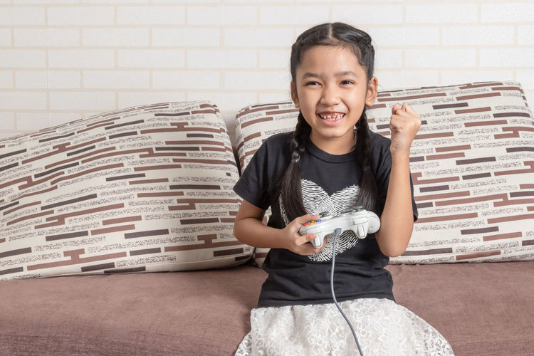 Portrait of a smiling girl holding camera