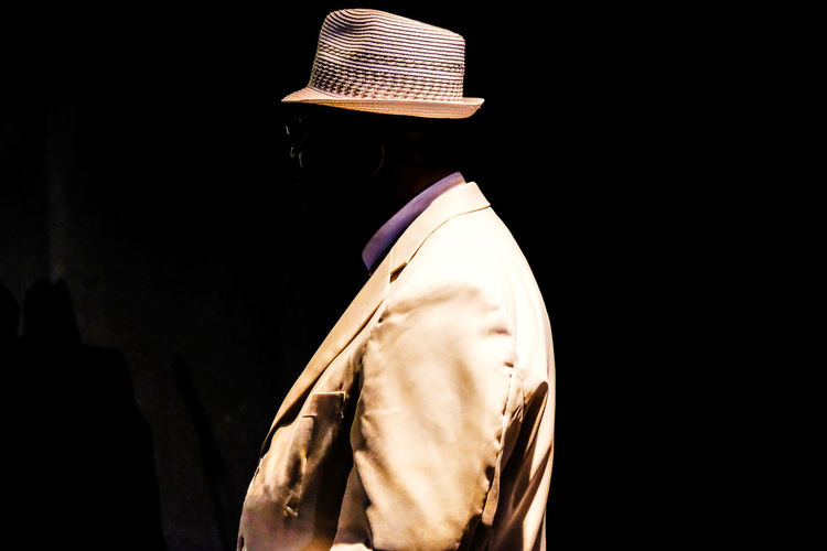 Side view of man with invisible face against black background