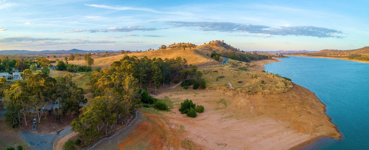 Aerial panorama of Lake Hume and yellow rolling hills at sunset. New South Wales, Australia Dusk High Up Horizon Lake Hume Village Landscape Murray River New South Wales  Outback Panoramic Reservoir Sky Sunrise Tranquil Scene Travel Locations Aerial Australia Australian Background Beautiful Border Countryside Dawn Drone  Environment Hill Hills Hume Hume Lake Lake Lookout Nature Nsw Outdoor Panorama River Scenic Sunset Travel Travel Destinations Trees Victoria View Village Water