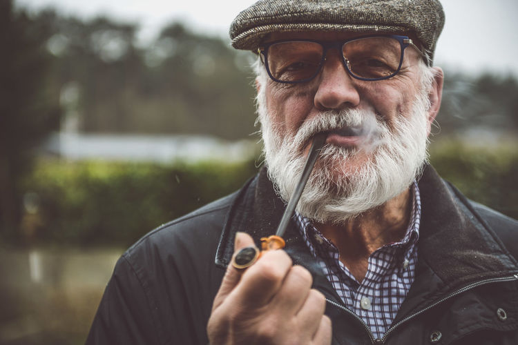 Portrait Of Senior Man Smoking At Park