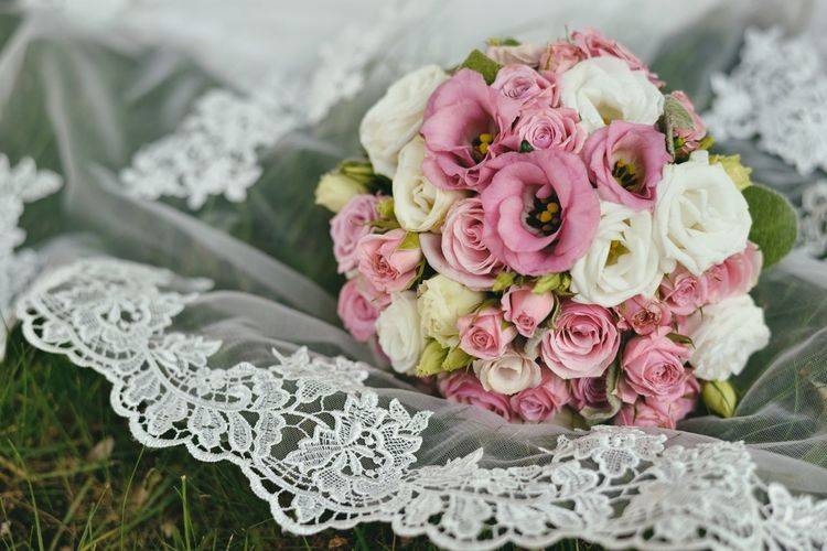 High Angle View Of Rose Bouquet On Lace Textile Over Grass
