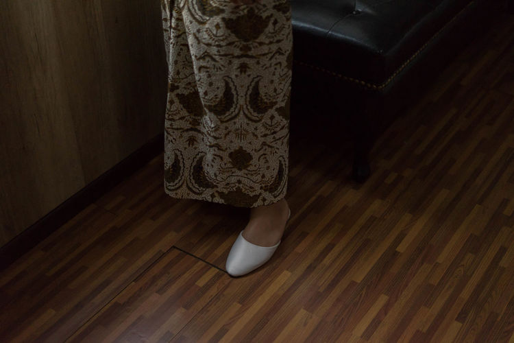 Low section of woman standing on wooden floor