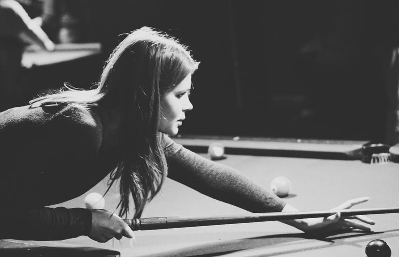 Side view of woman playing pool