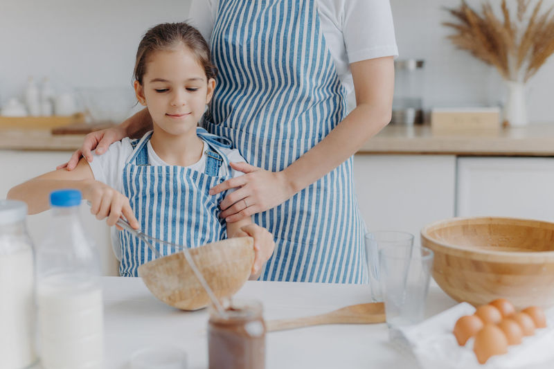 Midsection of mother standing with daughter mixing in bowl on table