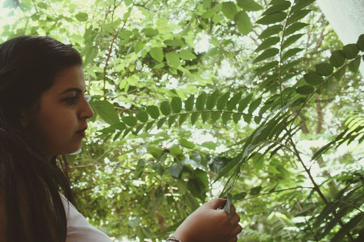 Side view of young woman touching plants at yard