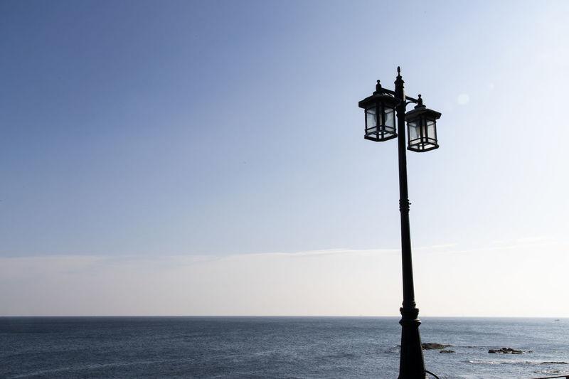 Street light by sea against clear sky