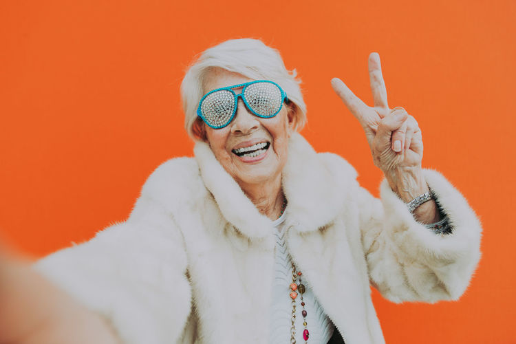 Portrait of smiling senior woman against orange background